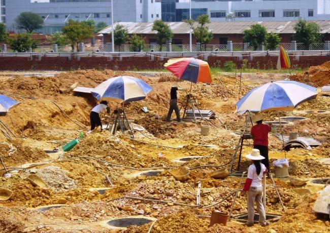 Hypergrotwh Arbeitsmigranten buddeln Fundierungschächte für einen modernen Wolkenkratzer.